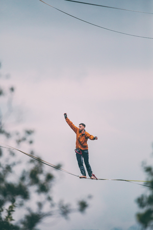 A man is walking along a stretched sling. Highline in the mountains. Man catches balance. Performance of a tightrope walker in nature. Highliner on the background of the sky.