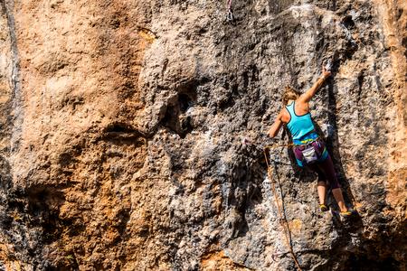 Une fille escalade un rocher. L'athlète s'entraîne dans la nature. La femme surmonte la route d'escalade difficile. Grimpeur fort. Passe-temps extrême.