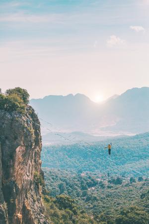 Un homme marche le long d'une écharpe tendue. Highline dans les montagnes. L'homme retrouve l'équilibre. Performance d'un funambule dans la nature. Highliner sur fond de montagnes. Banque d'images