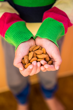 Children's hands hold almonds. A handful of nuts. The boy made hands in the shape of a heart. Proper nutrition. Healthy food. Vegetable protein. The child is carrying nuts to his mother.