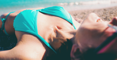 The girl sunbathes on the beach. Woman resting by the sea. Brunette in a swimsuit lying on the sand. Rest on the ocean coast.