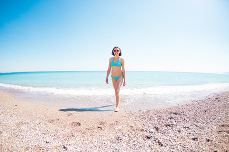A woman in a bathing suit walking along a stony shore. The girl looks at the ocean. Brunette resting on the beach of the Mediterranean Sea. Winter holidays in Turkey. The girl comes out of the water. Stock Photo