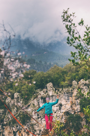 A woman is walking along a stretched sling. Highline in the mountains. Woman catches balance. Performance of a tightrope walker in nature. Highliner on the background of thunderclouds. Imagens