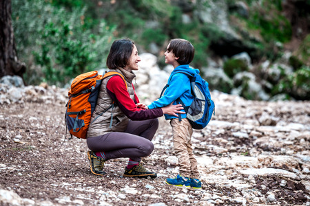 A woman walks with her son through the forest. The boy with his mother go hiking. A child with a backpack is in the park. Travel with children. The kid holds mom's hand.