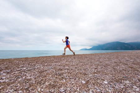 The girl runs along the beach. Woman trains in nature. Brunette runs on the background of the sea and the sunset cloudy sky. Running in the sand.