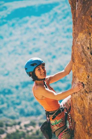 Ein Mädchen mit Helm klettert auf einen Felsen. Frau überwindet anspruchsvolle Kletterroute vor dem Hintergrund schöner Berge. Extremes Hobby. Klettern in der Türkei. Standard-Bild
