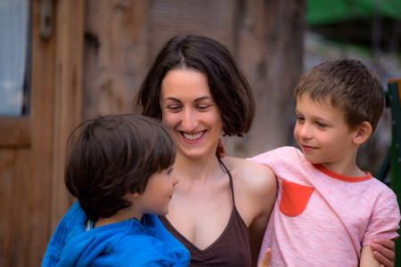 Frau umarmt Söhne auf der Terrasse eines Holzhauses. Jungen verbringen Zeit mit Mama. Junge Mutter geht mit Kindern. Eine glückliche Familie. Junge Brünette, die mit einem Kind herumalbert.