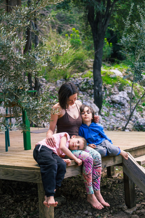 Woman hugging sons on the terrace of a wooden house. Boys spend time with mom. Young mother walks with children. A happy family. Young brunette fooling around with a child.