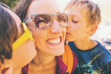 Kinder küssen Mama. Eine Frau umarmt ihre Söhne und lächelt. Der Junge umarmt Mutter und Bruder. Glückliche Mutterschaft. Standard-Bild