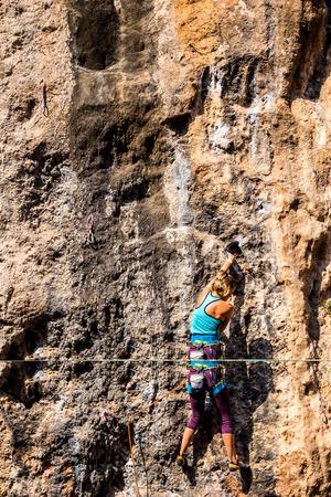 Ein Mädchen klettert auf einen Felsen. Der Athlet trainiert in der Natur. Frau überwindet schwierige Kletterroute. Starker Kletterer. Extremes Hobby. Standard-Bild