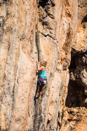 Een meisje beklimt een rots. De atleet traint in de natuur. Vrouw overwint moeilijke klimroute. Sterke klimmer. Extreme hobby. Stockfoto