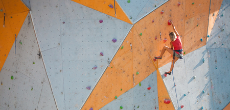 The climber trains on an artificial relief. A woman climbs a climbing route on a street climbing wall. Training in the hall. Strong girl involved in sports.