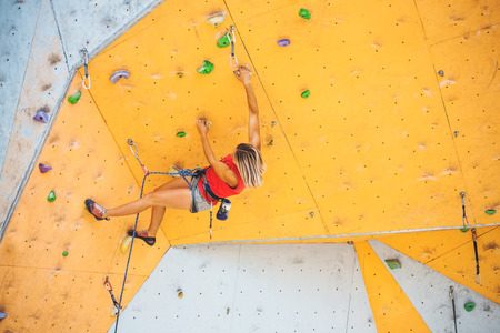 The climber trains on an artificial relief. A woman climbs a climbing route on a street climbing wall. Training in the hall.