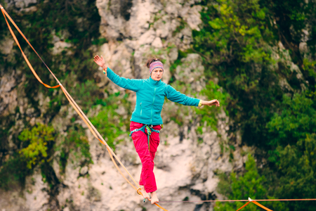 A woman is walking along a stretched sling. Highline in the mountains. Woman catches balance. Performance of a tightrope walker in nature. Highliner on the background of thunderclouds. Fall athlete.