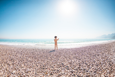Naked baby on the beach. A boy stands on the beach and looks at the sea. The child throws stones into the water. Vacation with children.