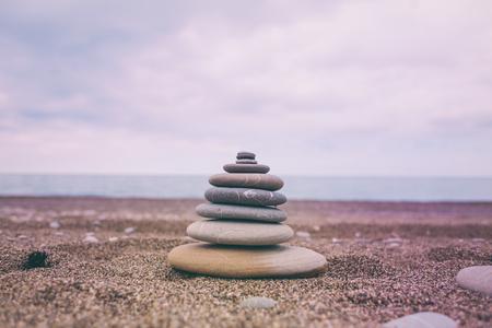 Turret of stones on the beach. Pyramid of flat stones in the sunset light. Sea coast. Sand beach. Pebbles.