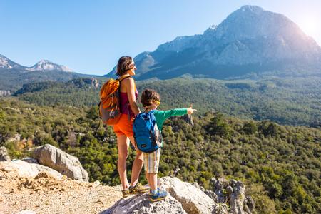 De jongen en zijn moeder staan op de top van de berg. Een vrouw reist met kind. Jongen met zijn moeder die naar de bergen kijkt. Reis met rugzakken. Wandelen en klimmen met kinderen.