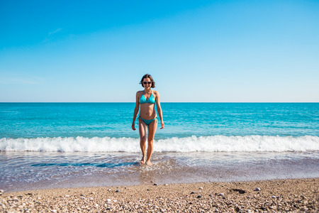 A woman in a bathing suit walking along a stony shore. The girl looks at the ocean. Brunette resting on the beach of the Mediterranean Sea. Winter holidays in Turkey. The girl comes out of the water.
