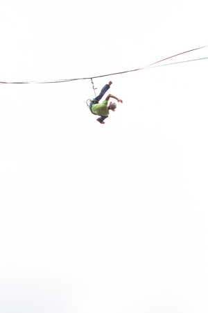 Highliner on a white background. Highline against the sky. A man catches the balance on a stretched sling. Barefoot tightrope walker hangs on a rope. Overcoming the fear of heights. Fall athlete.