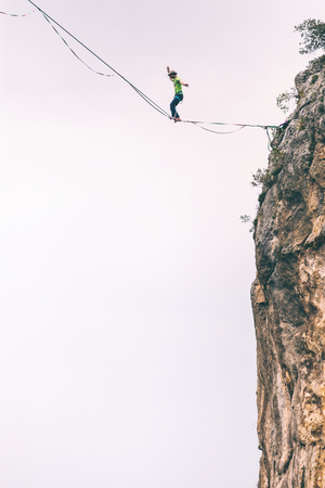 Highline on the background of the mountains makes a step. A man is walking along a stretched sling. Performance of a tightrope walker. Highliner balances over the abyss. Highline between two rocks. Stock Photo