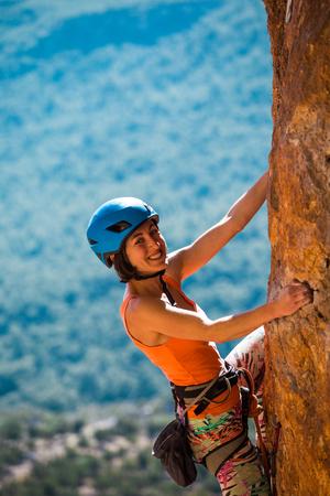 Ein Mädchen mit Helm klettert auf einen Felsen. Frau überwindet anspruchsvolle Kletterroute vor dem Hintergrund schöner Berge. Extremes Hobby. Klettern in der Türkei.