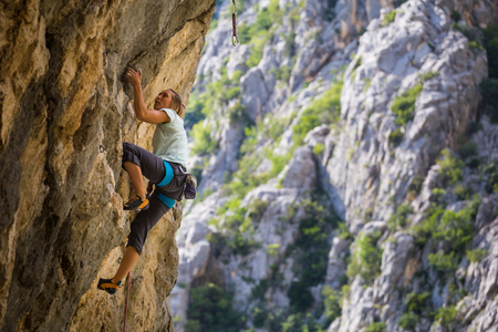 Rock climbing and mountaineering in the Paklenica National Park. A woman overcomes a challenging climbing route on natural terrain. Climber trains on the rocks of Croatia. Foto de archivo