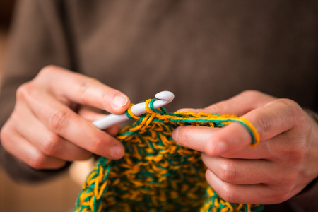 Woman crochets. Handwork. Crochet hook. Female hands closeup. Female hands hold the hook. Vintage carpet. Knitted plaid. Handmade. Home hobby. Standard-Bild