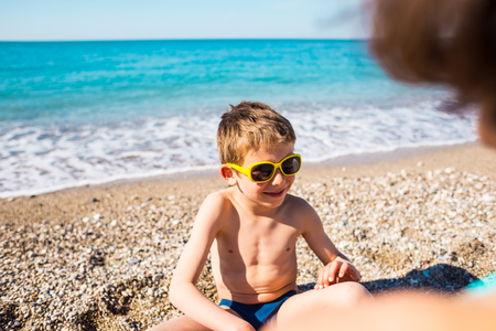 A boy in sunglasses plays with his mother on the beach. Portrait of a laughing child. Smiling baby sunbathes on the sea coast. Protect your eyes from sunlight. A woman is resting with her son.