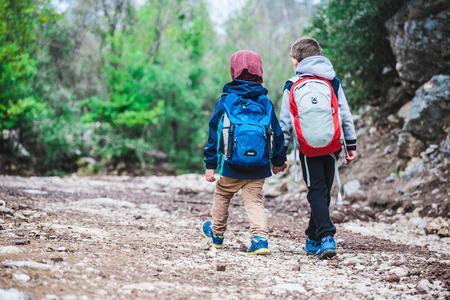 Due ragazzi con gli zaini stanno camminando lungo un sentiero nel bosco. I fratelli camminano insieme nel parco. Due amici si tengono per mano. Piccoli viaggiatori. I bambini trascorrono del tempo nella natura. Archivio Fotografico