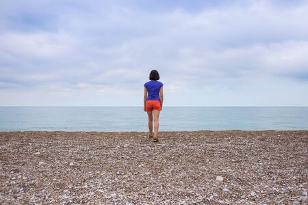 A woman walks alone on the sea coast. The girl looks at the sea and sunset. Evening walk on the sandy beach. Brunette resting on the ocean coast.