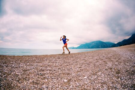The girl runs along the beach. Woman trains in nature. Brunette runs on the background of the sea and the sunset cloudy sky. Running in the sand. Ocean and mountains. Stock Photo