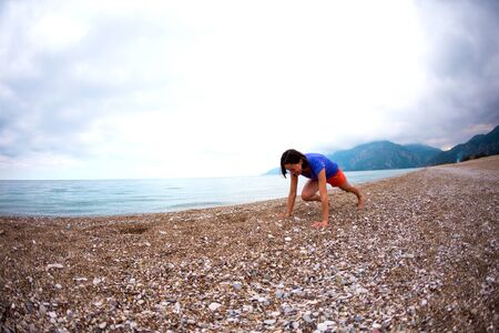 Woman doing sports on the beach. Push up. The girl does sports exercises on the background of the sea and mountains. Brunette does exercises for press. Active lifestyle. Warming up before running. Stock Photo