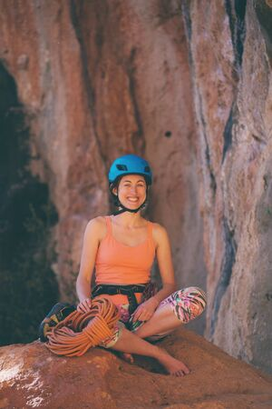 Climber sits near the rope and prepares to overcome the route. Slender girl holds climbing equipment. A woman in a helmet on the background of beautiful mountains. Rest after climbing. Stock Photo