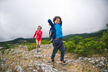 The boy runs away from his mother. The child is playing with mom. A woman is catching up with her son. Walk with mom on a mountain path. Holidays with children in nature.