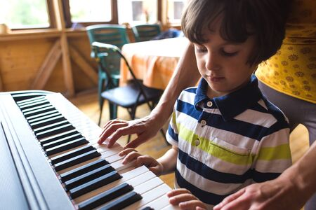 A woman teaches her son to play the piano. The boy masters the keyboard musical instrument. A child learns music. Childrens and womens hands on the piano keys. Music teacher. Tutor for a child. Reklamní fotografie