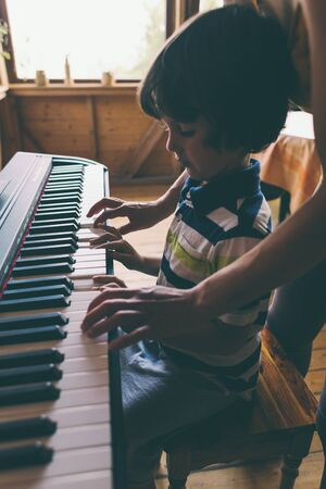 A woman teaches her son to play the piano. The boy masters the keyboard musical instrument. A child learns music. Childrens and womens hands on the piano keys. Music lesson. Tutor for a child. Reklamní fotografie