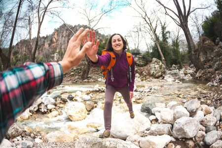 Girl greets friend. A woman with a friend is walking in the woods. The couple travels to scenic places. The girl gives five. Gesture of greeting. A tourist crosses a mountain river to a ford. Imagens