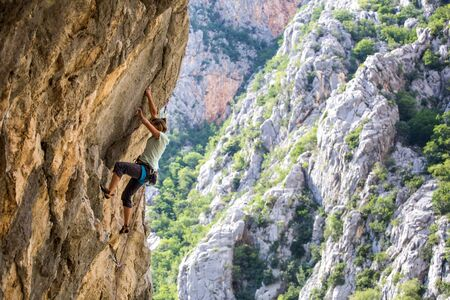 Rock climbing and mountaineering in the Paklenica National Park. A woman overcomes a challenging climbing route on natural terrain. Climber trains on the rocks of Croatia. Banque d'images