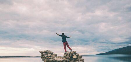 La ragazza sta su un mucchio di pietre e guarda il mare. Donna che riposa sulla costa del mare. Il turista esplora le attrazioni della Croazia. Siluetta femminile contro il cielo al tramonto.