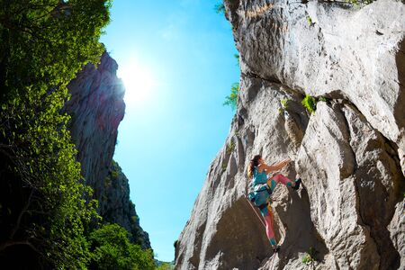 Rock climbing and mountaineering in the Paklenica National Park. A woman overcomes a challenging climbing route on natural terrain. Climber trains on the rocks of Croatia. 스톡 콘텐츠