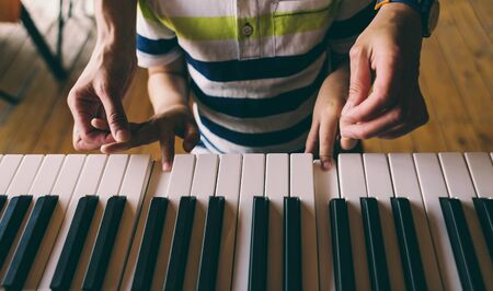A woman teaches her son to play the piano. The boy masters the keyboard musical instrument.