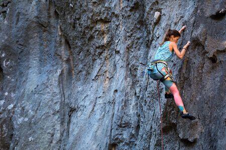 Kletterer überwindet anspruchsvolle Kletterroute. Ein Mädchen klettert auf einen Felsen. Frau im Extremsport tätig. Extremes Hobby.