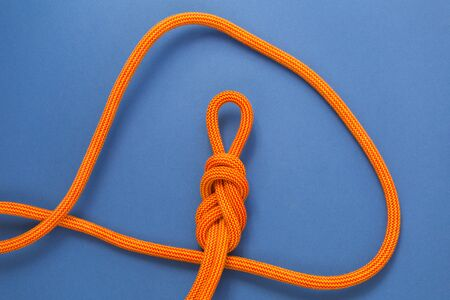 Orange climbing rope on a blue background. Safety knot. The knot the eight for safety. 版權商用圖片