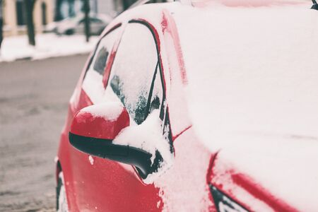 Snow covered red car. Parked vehicle close up. The machine is covered with hoarfrost. Winter snowfall.