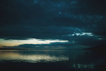 Night sky and sea. The setting sun and calm water. Sunset sky with clouds. Dark ocean water. Banque d'images