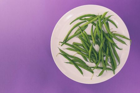 Asparagus beans on a white plate. A legume plant. Boiled beans. Vegetarian dish on a purple background.