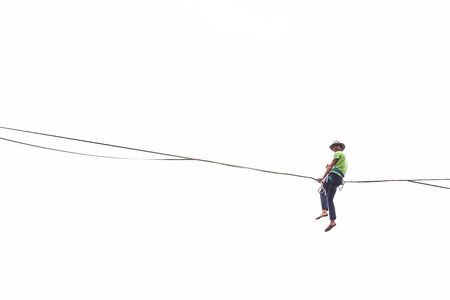 Highline on a white background. A man sits on a stretched sling. Performance of a tightrope walker. Highliner balances over the abyss. The athlete is trying to get up after a fall. Banco de Imagens
