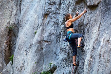 Climber overcomes challenging climbing route. A girl climbs a rock. Woman engaged in extreme sport. Extreme hobby. Foto de archivo - 127584786