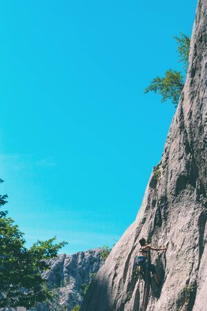 Climber overcomes challenging climbing route. A girl climbs a rock. Woman engaged in extreme sport. Extreme hobby. Foto de archivo - 127584836