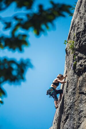 Climber overcomes challenging climbing route. A girl climbs a rock. Woman engaged in extreme sport. Extreme hobby. Foto de archivo - 127584843